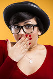 Astonished nerd girl. Beautiful girl with a astonished expression, wearing a hat and nerd glasses over a yellow background Royalty Free Stock Photos