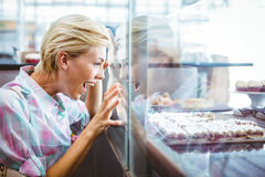 Astonished pretty woman looking at cup cakes Royalty Free Stock Photo