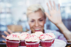 Astonished pretty woman looking at cup cakes Royalty Free Stock Photos