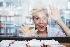 Astonished pretty woman looking at cup cakes Stock Images