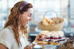 Astonished pretty woman pointing at cakes Stock Photo