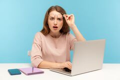 Free Astonished Smart Woman Taking Off Eyeglasses And Looking With Open Mouth In Amazement, Working On Laptop Stock Photography - 182442352