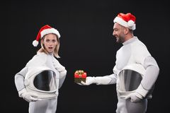 Astonished spacewoman is accepting christmas present from positive spaceman stock images