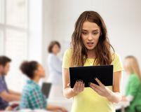 Astonished student girl with tablet pc at school stock photos