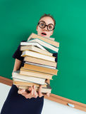 Astonished student with pile of books in her hands, staring at you with her mouth open. Photo of young girl wearing glasses. Back to school Stock Photos