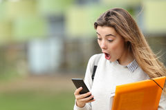 Astonished student receiving news on a smart phone Stock Photos