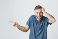 Astonished surprised bearded male with smile looks happily at camera, wears blue casual t -shirt, indicates with index. Astonished surprised bearded male with royalty free stock photography