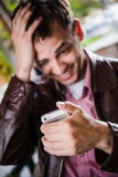 Astonished and surprised man smiling reading text message on smart phone at cafe outdoors. Selective focus Royalty Free Stock Image