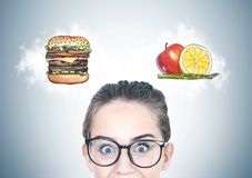 Astonished teen girl in glasses, food choice stock photos