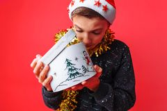 Teen guy in Santa hat and with tinsel around his neck opening with interest gift box for Christmas, on red background stock photography