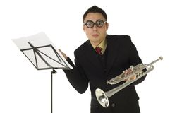 Astonished trumpeter. Standing in front of sheet music and looking at camera. Front view. White background Stock Image