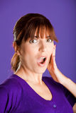 Astonished woman. Portrait of a beautiful woman with an astonish expression, over a violet background Royalty Free Stock Photos