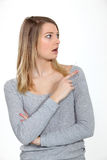 Astonished woman. Looking and pointing her finger sideways Royalty Free Stock Images