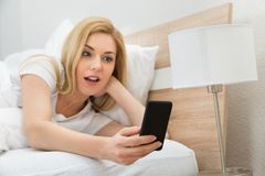 Astonished Woman In Bed With Mobile Phone Royalty Free Stock Image
