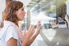Astonished woman touching window with one hand Royalty Free Stock Image