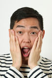 Astonished young Asian man covering his face with palms Royalty Free Stock Images