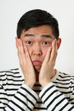 Astonished young Asian man covering his face with palms Stock Photo
