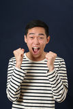 Astonished young Asian man laughing and shaking two fists Stock Photo