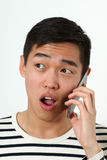 Astonished young Asian man using a smartphone Royalty Free Stock Images