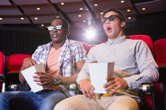 Astonished young friends watching 3d film Stock Photos