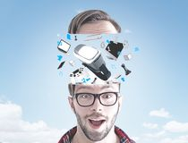 Astonished young man and gadgets in the sky Stock Photo