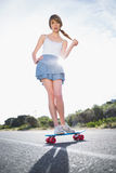 Astonished young woman balancing on her skateboard Stock Image