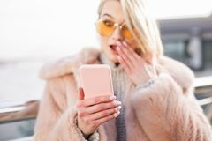 Astonished young woman is holding her mobile phone. Shocking news. Close up of pink smartphone in hand of surprised girl. She is looking at screen of gadget with royalty free stock photography