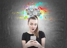 Astonished young woman, smartphone, cog brain. Astonished young woman with a ponytail wearing a black T shirt and looking at her smartphone screen with an open royalty free stock photos