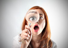 Astonishing discover. Young woman with astonished expression holding a magnifying glass Stock Photography