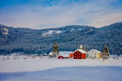 Astonishing outdoor view of traditional Norwegian mountain red houses of wood covered with snow in the roof in stunning. Nature mountain background in Norway Stock Photos