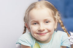 Astonishing portrait of a smiling cute little girl. Sitting indoors Royalty Free Stock Image