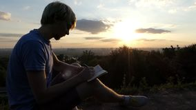 Smart man writes a fairy tale on a lawn at sunset in slo-mo