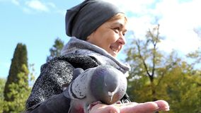 A smiling woman feeds doves on a sunny square in slo-mo. An astonishing view of a happy woman feeding several grey doves from her hands in slow motion. She stock video footage