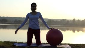 Slim woman kneels and bends aside near a fitball at sunset. An astonishing view of a sportive woman who kneels and bends aside while touching a big red fitball stock video footage