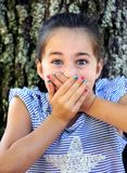 Astonishment With Hands Over Mouth. Little girl holds in her scream of surprise as she holds her hands over her mouth. She is sitting outside by a tree, and stock photo