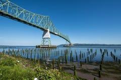 Astoria-Megler bridge, which goes over the Columbia River in Astoria Oregon. Dock pillars in foreground stock photo
