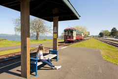 Astoria Oregon`s Waterfront Trolley Stop. Astoria, Oregon,USA - April 7, 2016: A young girl waits at a stop to ride the trolley along the Columbia River on Royalty Free Stock Photos