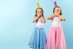 Astounded twins. Portrait of twin girls in beautiful dresses and crowns showing their amazement Stock Photos