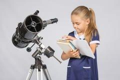 Astrónomo de la colegiala que hojea a través de los libros para encontrar la información correcta en el soporte del telescopio Imágenes de archivo libres de regalías