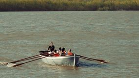 Astrakhan, Russia, 27 of April 2018: Girl-scout Lead Boy-scouts Rowing Team on the Water. Wooden oars rowing water. Astrakhan, Russia, 27 of April 2018: Girl stock video