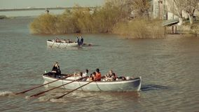 Astrakhan, Russia, 27 of April 2018: Two Boats Boy-scouts Rowing Team on the Water. Wooden oars rowing water. Astrakhan, Russia, 27 of April 2018: Two Boats Of stock footage