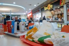 Astrakhan Russia 13 Feb. 2019: KFC fastfood takeaway cup with famous face of founder on tray among fastfood packs. KFC stock image