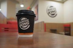 Astrakhan, Russland - 15. April 2019: Burger King Coffee-To-Go Takeaway Cup auf Tabelle an unscharfem Restaurant-Hintergrund lizenzfreie stockfotos