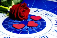 Astral love. Red rose and heart shapes on an astrological plan Stock Photo