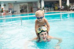 Astride. Boy sitting astride on his mother�s shoulders while she swimming in the pool Stock Image