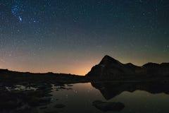 Astro满天星斗的天空在湖反射了在阿尔卑斯的高处 猎户星座星座发光 库存照片