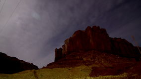 Astro Mountain Tracking Time-lapse. The Moon and clouds passing over some mesas in Utah's scenic Monument Valley revealing the night sky with dozens of stars stock video footage
