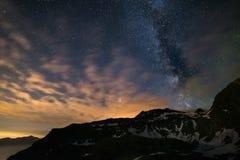 Astro nocne niebo, Milky sposobu galaxy gra główna rolę nad Alps, burzowy niebo, Mars planeta poza chmury, snowcapped pasmo górsk Zdjęcie Stock