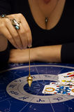 Astrologer. Female astrologer with esoteric instruments pendulum and tarots Stock Images