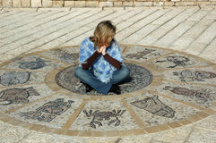 Astrological wheel. Blond woman sitting on antic astrological wheel Royalty Free Stock Images